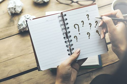 woman written question mark on notepad in office